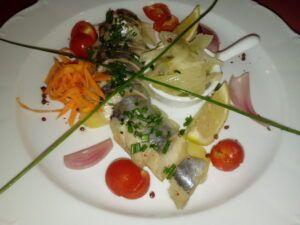 porce sleďů v oleji naložená na talíř a ozdobená oblohou